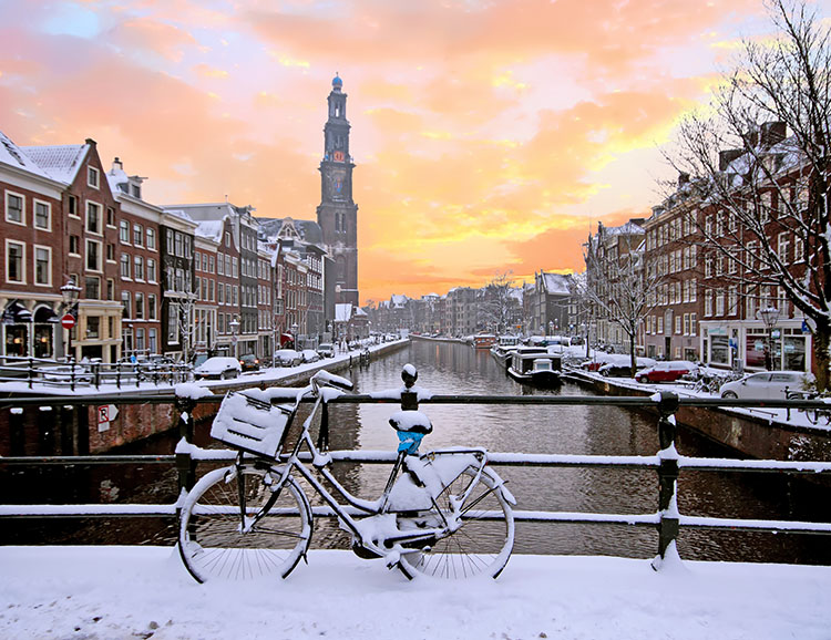 Amsterdam covered with snow with the Westerkerk in winter in the