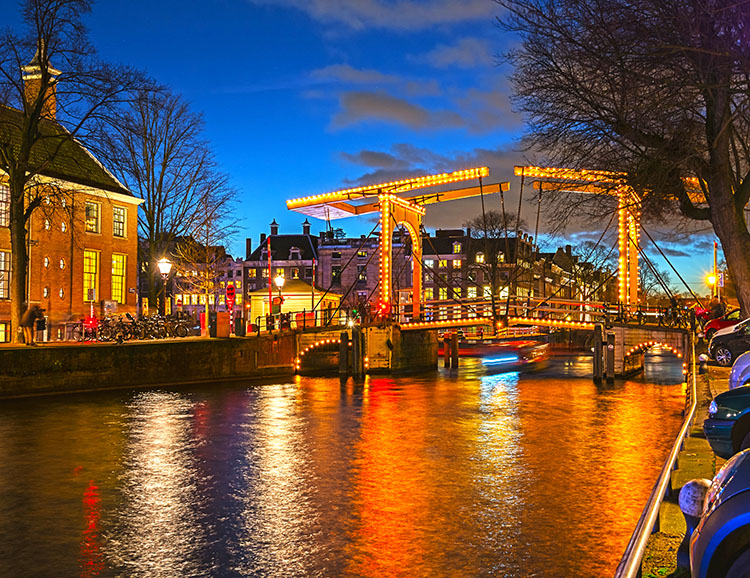 Illuminated bridge in the old town of Amsterdam in the evening